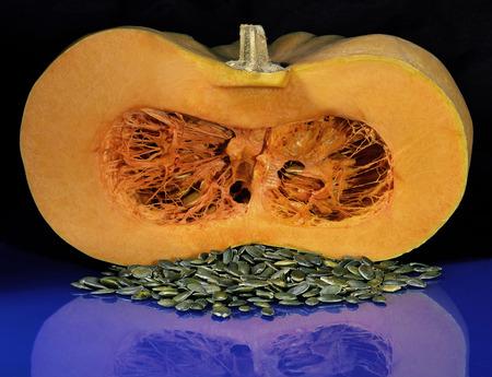 longitudinal: longitudinal section of orange pumpkin and peeled seeds on a blue table
