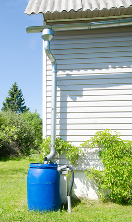 metal pipes for draining rainwater in a plastic barrel in a country house Stock Photo - 59985888