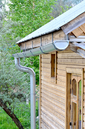 rainwater: metal pipes for draining rainwater in a plastic barrel in a country house