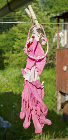 pink rubber gloves old torn damaged burnt due to solar radiation and light on a wooden clothespin and rope