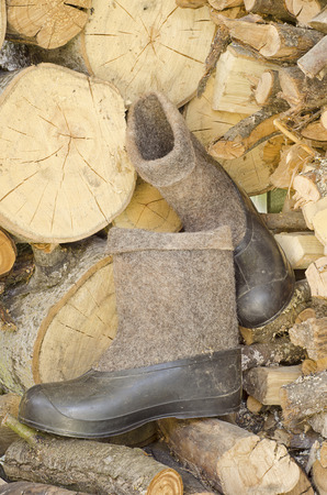 galoshes: a pair of dirty old black rubber galoshes and boots grey wool sheepskin on the wooden floor next to the wood in the daytime