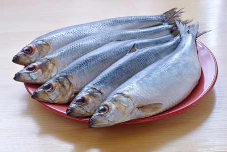 five fresh untreated fish of the herring are laid on ceramic brown plate and wooden table