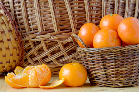 cleansed: pile of tangerines in a small basket and have not been fully cleansed Mandarin on the table amid the basket Stock Photo
