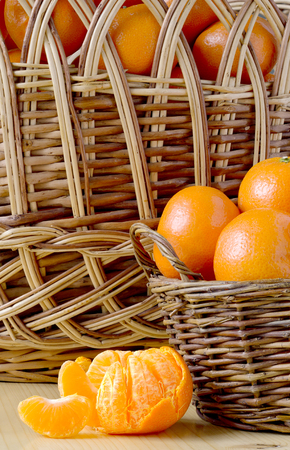 cleansed: pile of tangerines in a small and a large basket and have not been fully cleansed with the Mandarin slices on the table in the background of a wicker basket