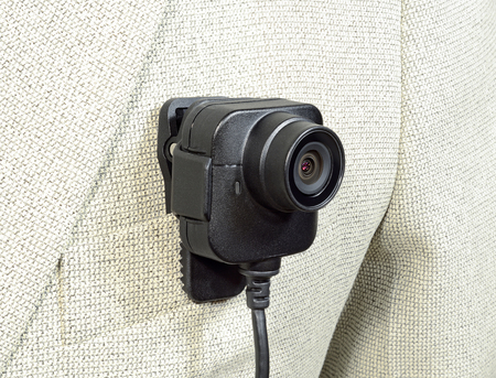 lens from the camcorder, security police body camera with power cord in black color on a white suit jacket Reklamní fotografie