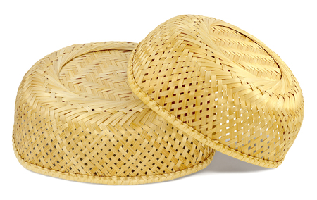 inverted: two inverted wicker basket material straw light yellow color, small basket lies on big basket, isolated on white background Stock Photo