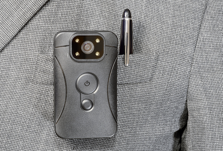 black plastic body camera or DVR is fixed by the clip on pocket, plaid jacket and metal ball pen Stock Photo