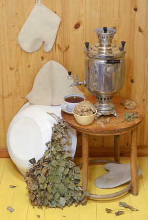 Set for bath: shiny metallic old samovar, Cup, tea Cup, bowl with cookies on the wooden round table, a broom made of birch leaves, white, metal, bowl, hat and gloves in the bath in Russia Stock Photo