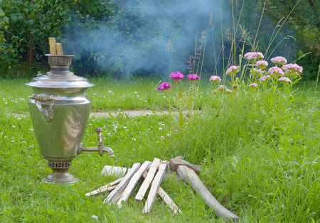shiny samovar is heated by the fire burning splinters of wood and it emits white smoke; and the samovar standing on a green grass on a background of different colors of red and pink, next to a samovar lies the axe and the wood. day in Russia closeup