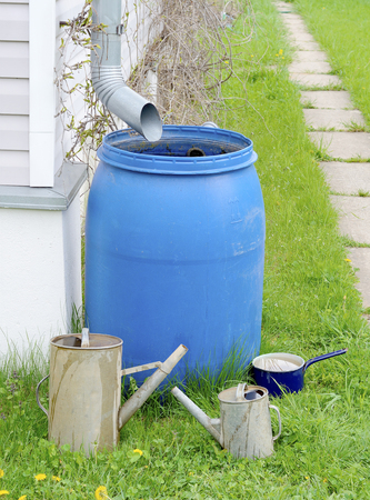 Blue plastic barrel to drain rainwater out of the sewer pipes, a small and a big old garden watering cans of galvanized metal and metallic blue pot on green grass in summer
