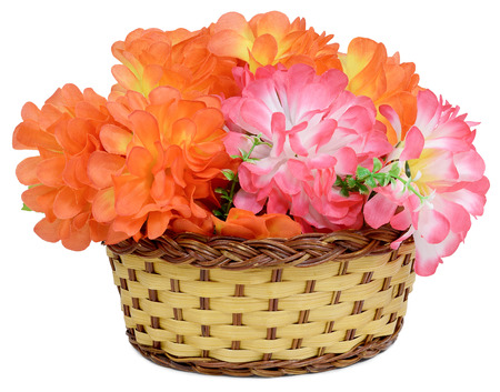Large bouquet in a basket of Artificial flower rose peony red white yellow and orange bright color made of synthetic fabric and plastic. Items pictured close up isolated on white background. Stock Photo