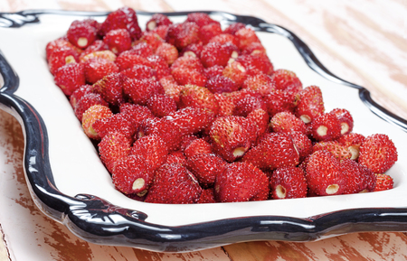 A fragment of a crop of strawberries lies on a white ceramic tray on a brown wooden table close-up. 免版税图像