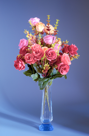 Still life Bouquet artificial rose flowers red, pink yellow in glass vase on blue background.