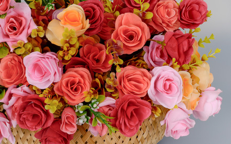 A fragment of a bouquet of artificial rose flowers red, pink yellow in a basket on a gray background. Banco de Imagens