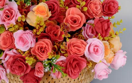 Un frammento di un bouquet di fiori rosa artificiali rossi, rosa gialli in un cesto su sfondo grigio. Archivio Fotografico