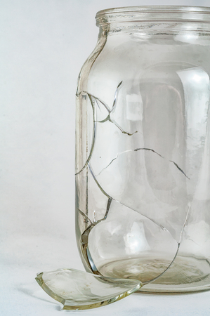 A fragment of one glass jar damaged cracked and cracked, splinters on a white background close-up.