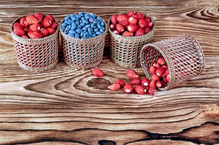 Four serving baskets with berries strawberries and blueberries, blueberries. Arranged horizontally on a wooden background close-up.