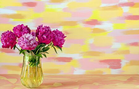 Horizontal image of a Bouquet of flowers of red pink white peonies in a glass yellow vase on a mottled yellow blue background. Stock Photo