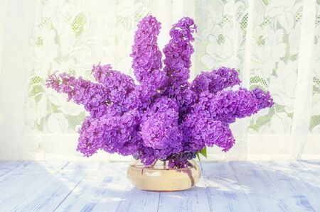 A bouquet of branches of lilac flowers purple, purple in a glass round vase on a wooden white table in the background sunlight close-up.