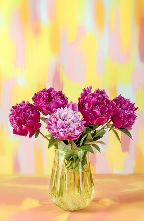Bouquet of flowers of red pink white peonies in a glass yellow vase on a mottled yellow blue background.