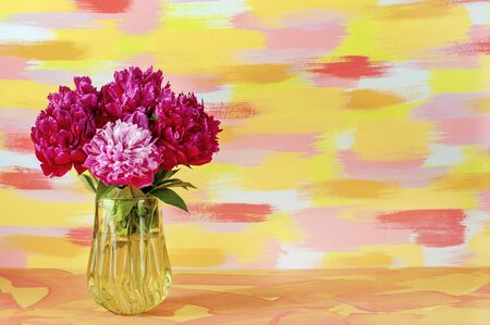 A bouquet of flowers of delicate red pink white peonies in a glass yellow vase on a mottled yellow red background. Stock Photo