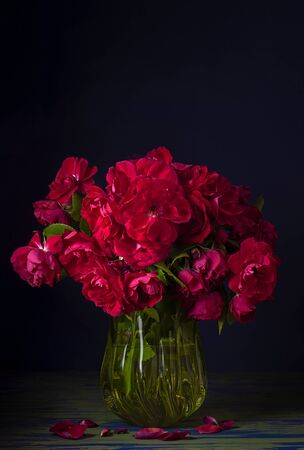 A large bouquet of red rose and rose hip flowers in a yellow glass vase on a dark blue background. Stock Photo - 140164041