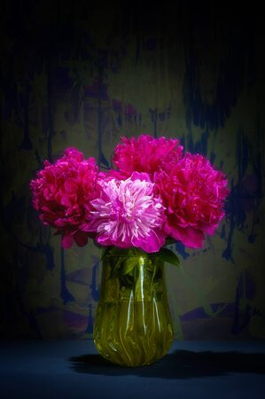 A bouquet of flowers of red pink white peonies in a glass yellow vase on a mottled dark blue background. Stock Photo