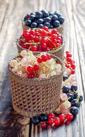 Three serving baskets with red, white, and black currant berries. Arranged vertically on a wooden background close-up. Stock Photo