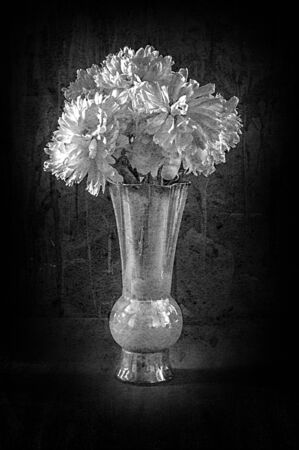 Black and white funeral image of a stone monument of the grave a bouquet of white peonies in a ceramic vase.