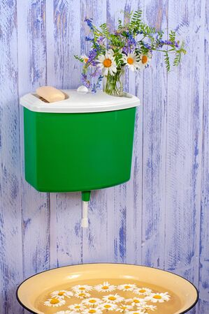 A plastic green washstand on a purple fence on which a glass with a bouquet of flowers and a bar of soap. Under the wash basin with chamomile petals. Stock Photo