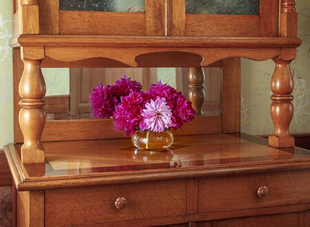 Vintage mahogany sideboard furniture with a vase with a bouquet of peony red and pink flowers that are reflected in the mirror.