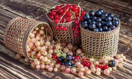 Three serving baskets with red, white, and black currant berries. Scattered on a wooden table. On a wooden background close-up.