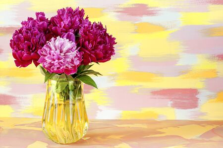 A bouquet of flowers of delicate red pink white peonies in a glass yellow vase on a mottled yellow blue background. Stock Photo