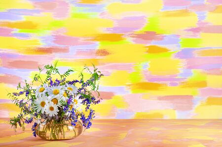 A bouquet of wild summer field flowers of chamomile and mouse peas in a glass vase on a mottled yellow-red-blue background. Stock Photo - 137456434