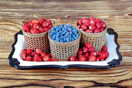Three serving baskets of strawberries and blueberries. On a white ceramic tray on a wooden table close-up.