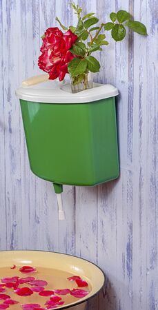 The washbasin is a plastic green on a purple fence on which there is a vase with a rose flower. Under the washstand is a basin with rose petals. Stock Photo