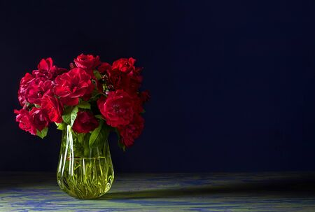 Rosehip bouquet of red roses in a glass yellow vase on a colorful blue table and on a dark blue background for the desktop. Stock Photo