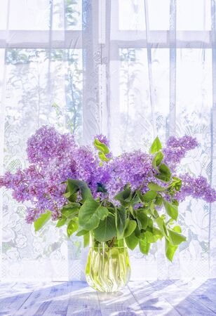 A bouquet of branches of lilac purple, purple flowers in a glass yellow vase on a wooden white table in the contrasting sunlight.
