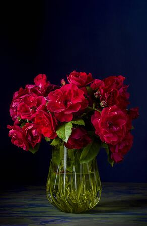 Vertical image of a Bouquet of rosehip red roses in a glass yellow vase on a mottled blue table and on a dark blue background for the desktop.