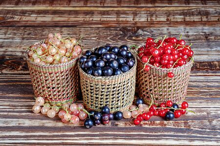 Three serving baskets with red, white, and black currant berries. Arranged horizontally on a wooden background close-up.