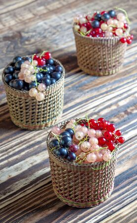 Three serving baskets with red, white, and black currant berries. Scattered vertically on a wooden table. On a wooden background close-up.