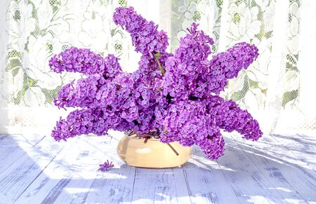 Horizontal image of a Bouquet of branches of lilac flowers purple, purple in a glass round vase on a wooden white table in the background sunlight close-up. Stock Photo