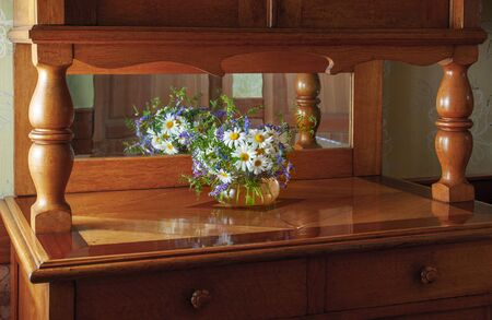 Vintage furniture mahogany sideboard with a vase with a bouquet of flowers of field daisies and mouse peas, which are reflected in the mirror.
