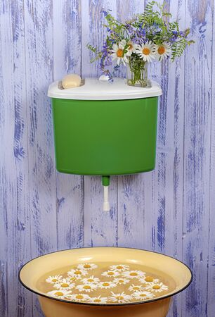 A plastic green washstand on a purple fence with a glass vase with a bouquet of flowers and a bar of soap on it. Under the wash basin with chamomile petals. Stock Photo