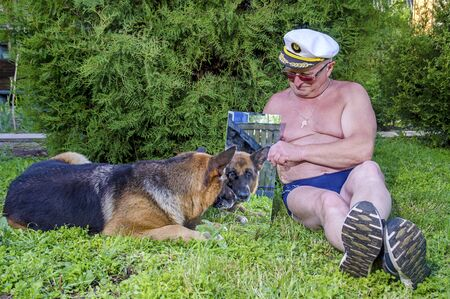 An elderly pensioner with a German shepherd dog shows the dog a mirror in the countryside in the garden. The man is dressed in swimming trunks, in summer in Sunny weather. Stockfoto