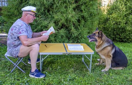An elderly pensioner reads a magazine with a German shepherd sitting at a table in the countryside in the garden. Summer in Sunny weather.