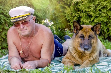 A man an elderly pensioner cheerful smiles and a German shepherd dog lie next to him on the grass in a rural garden. Summer in Sunny weather.