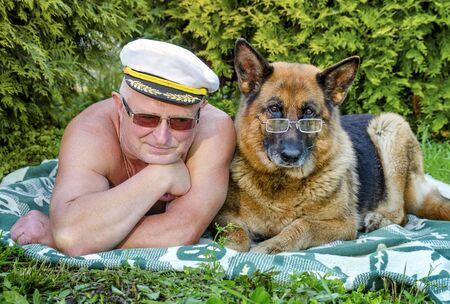 Friends, an Elderly pensioner and a German shepherd with glasses lie side by side on a blanket in a rural garden. Summer in Sunny weather.