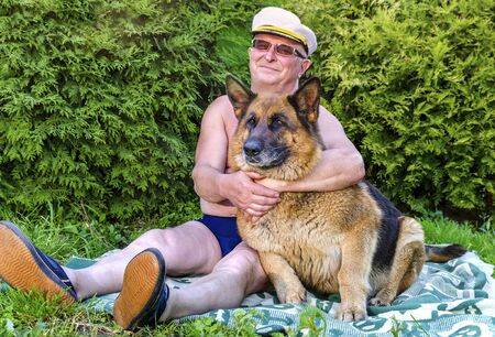 A man an elderly pensioner a cheerful smile and a German shepherd dog sit and hug next to each other on the grass in a rural garden. Summer in Sunny weather. Stock Photo - 140901631