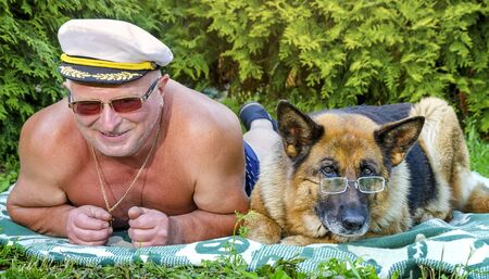 Cheerful friends, an elderly pensioner and a German shepherd with glasses lie side by side on a blanket in a rural garden. Summer in Sunny weather. Stock Photo